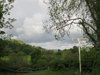 Three-directional road sign in Wales with looming gray clouds, near the English border.