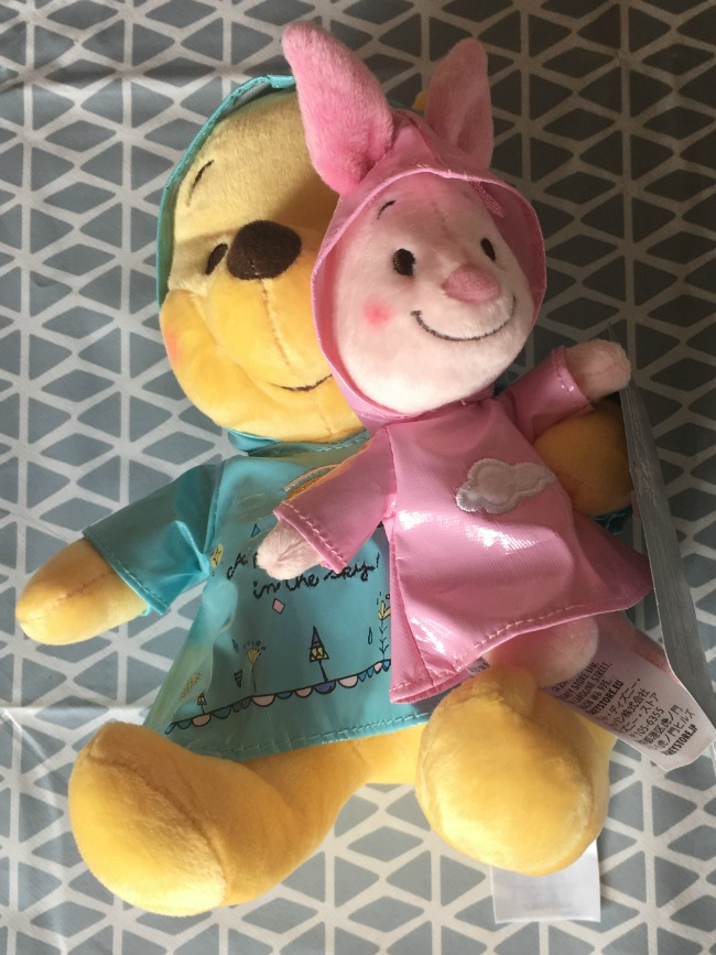 Disney-Store-pooh-bear-and-piglet-wearing-Easter-rain-coats-poohs-coat-is-blue-and-piglets-is-pink-with-rabit-ears