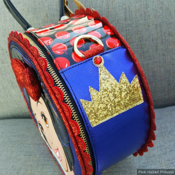 side of round handbag in apple print with gold glitter crown applique detail