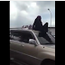 Omg! Watch video of angry wife sit on husband's car roof to stop him driving off with girlfriend (video)