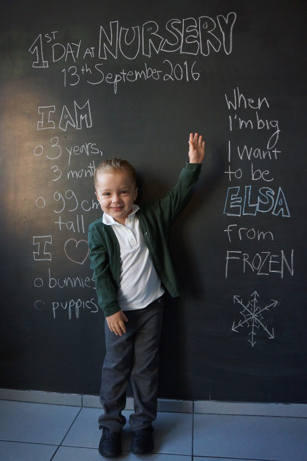 toddler standing in front of a blackboard with nursery drawings