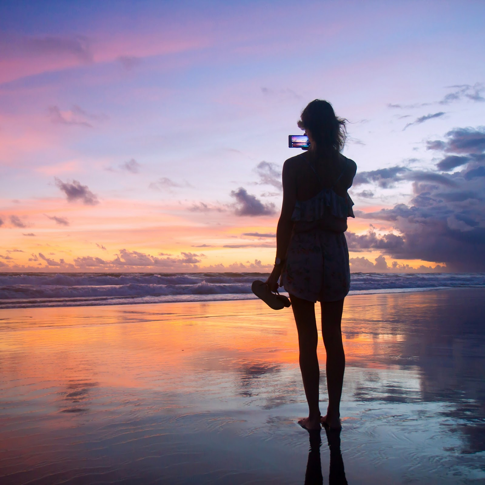 Fashion and travel blogger, Alison Hutchinson, snapping a photo of the sunset in Bali, Indonesia