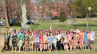a group of students with a lot of colorful powder on their clothes at the holi celebration