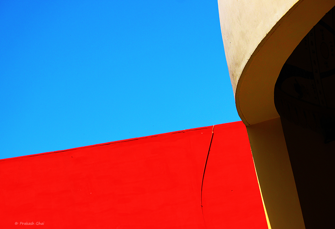 A minimalist photo of Red wall against the blue sky.