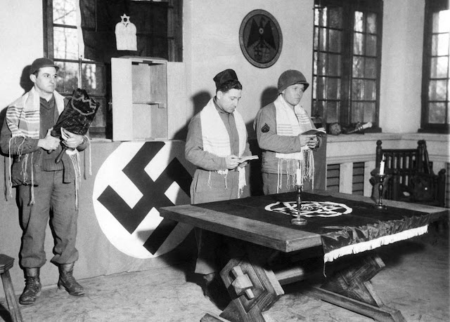 Pfc. Abraham Mirmelstein of Newport News, Virginia, holds the Holy Scroll as Capt. Manuel M. Poliakoff, and Cpl. Martin Willen, of Baltimore, Maryland, conduct services in Schloss Rheydt, former residence of Dr. Joseph Paul Goebbels, Nazi propaganda minister, in Münchengladbach, Germany on March 18, 1945. They were the first Jewish services held east of the Rur River and were offered in memory of soldiers of the faith who were lost by the 29th Division, U.S. 9th Army.