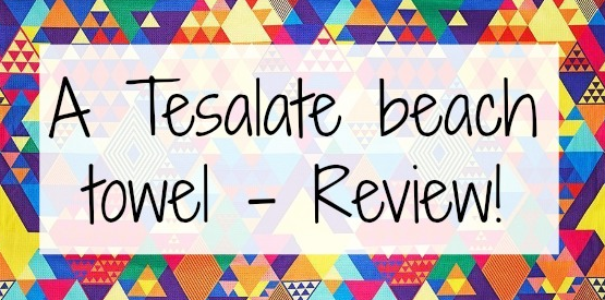 Text saying Tesalate beach towel review on a background of a brightly coloured towel