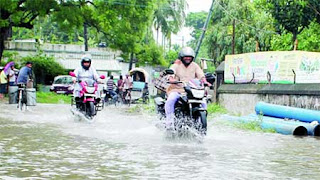 Motorbikes screech through a water-logged road after an hour-long rain in Balurghat