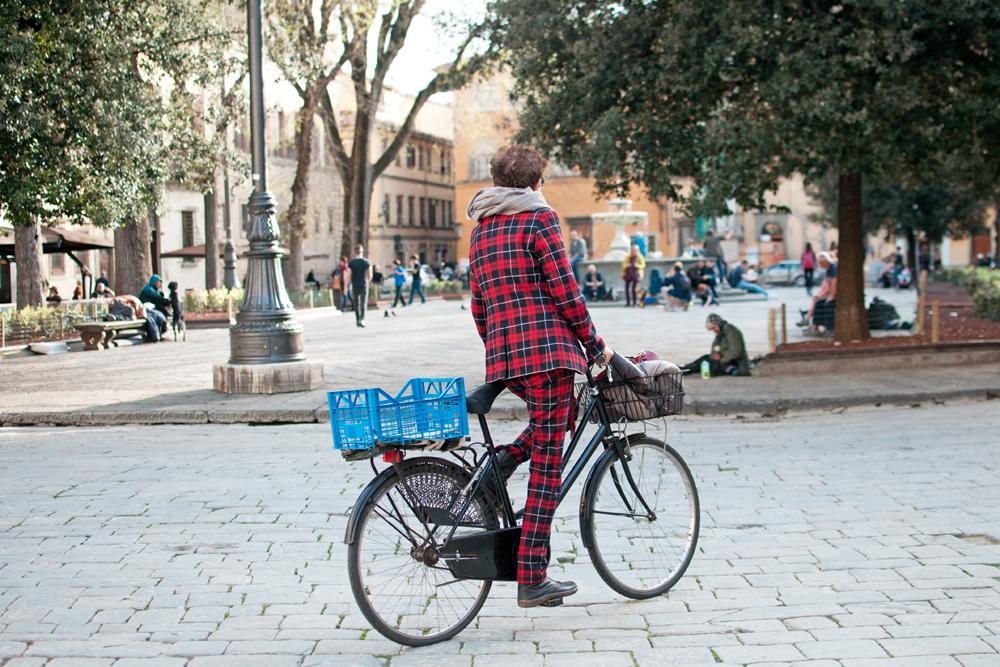 Une femme habillée avec un ensemble à motif écossais est sur un vélo sur une place florentine