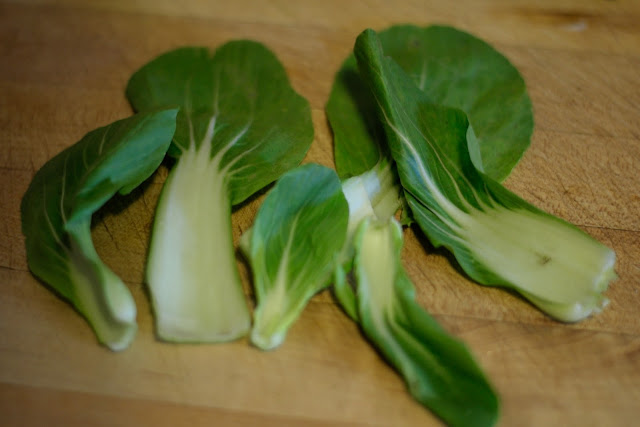 The head of Bok Choy broken into separate pieces onto a cutting board.