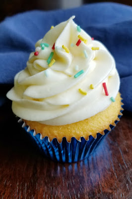 lemonade Russian buttercream piped on a lemon cupcake and dusted with sprinkles