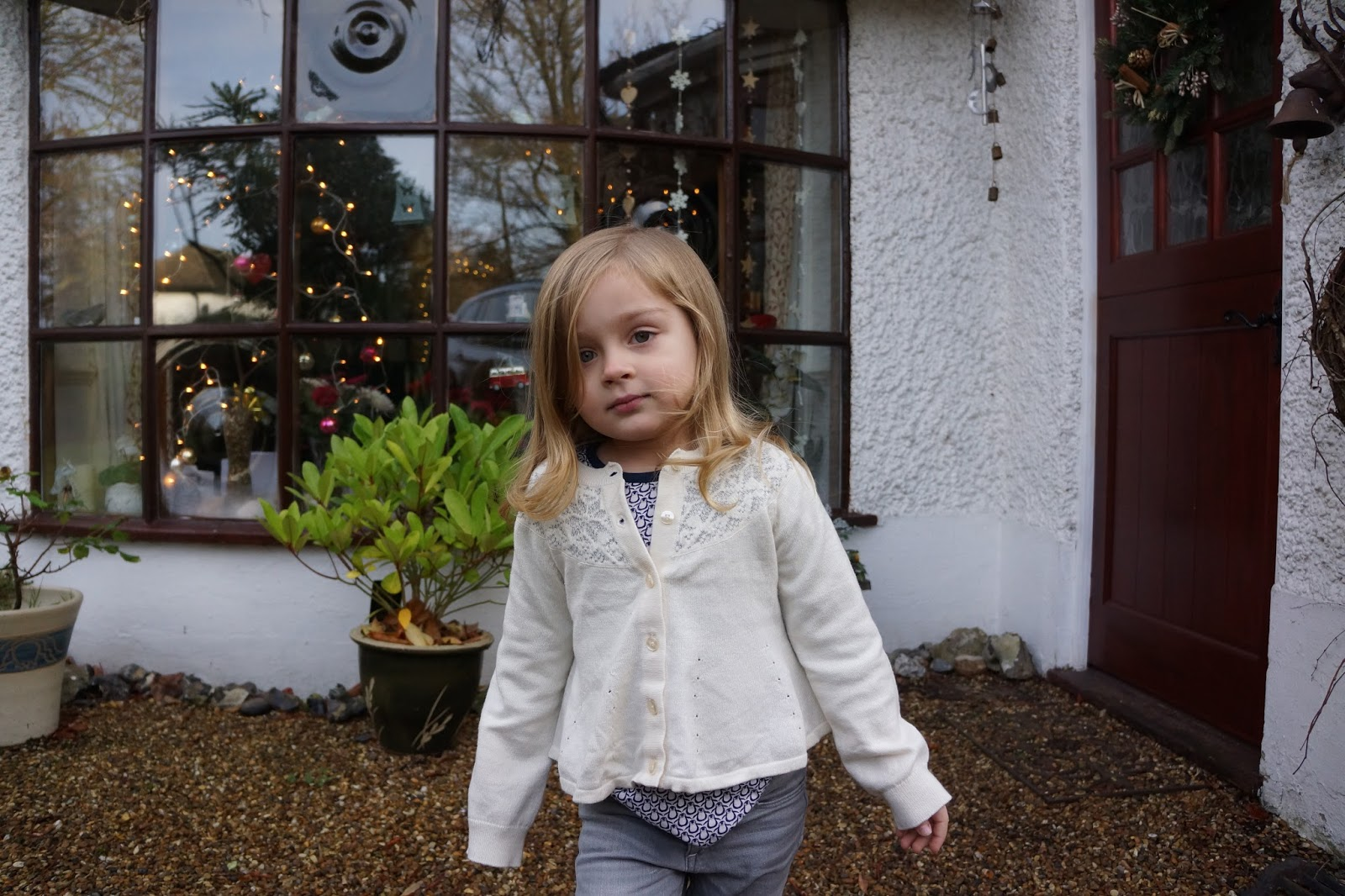 young girl in a white christmas cardigan