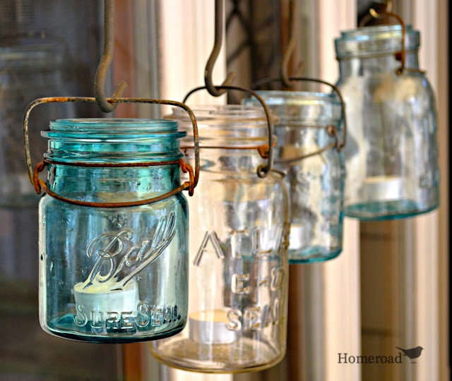 Mason jars hanging in a row with candles
