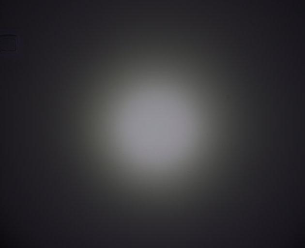 Wiązka światła latarki Olight M2R na ścianie