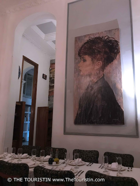 Set tables and art in the background at restaurant Le Chansonnier in Havana in Cuba
