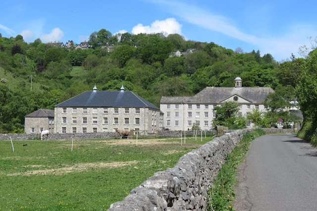 View down a lane to mill buildings converted into apartments, below a tree covered hillside.