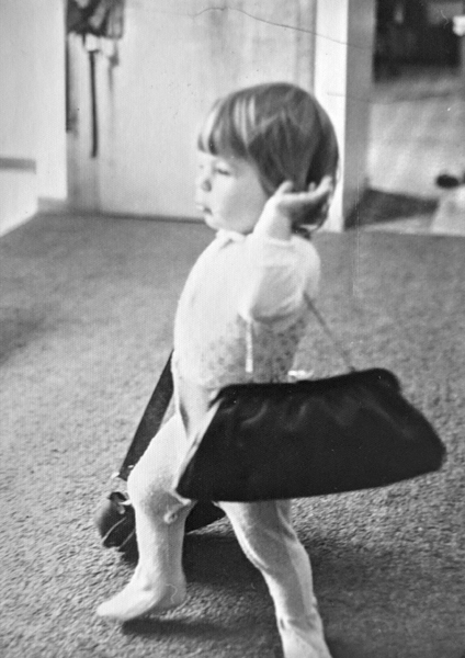 black and white image of me as a baby in pajamas, walking around with a purse slung over my shoulder and dragging another bag on the ground with the opposite hand