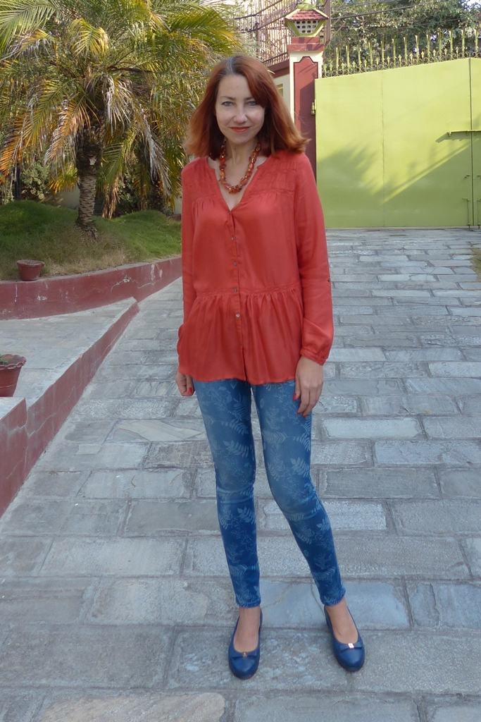 Outfit in orange and blue: printed skinny jeans, orange top and blue flats