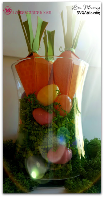 This is a picture of a vase filled with green paper grass, plastic pastel Easter eggs, and carrot treat boxes.