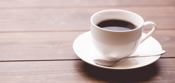 木調のテーブルに出された白いカップのコーヒー