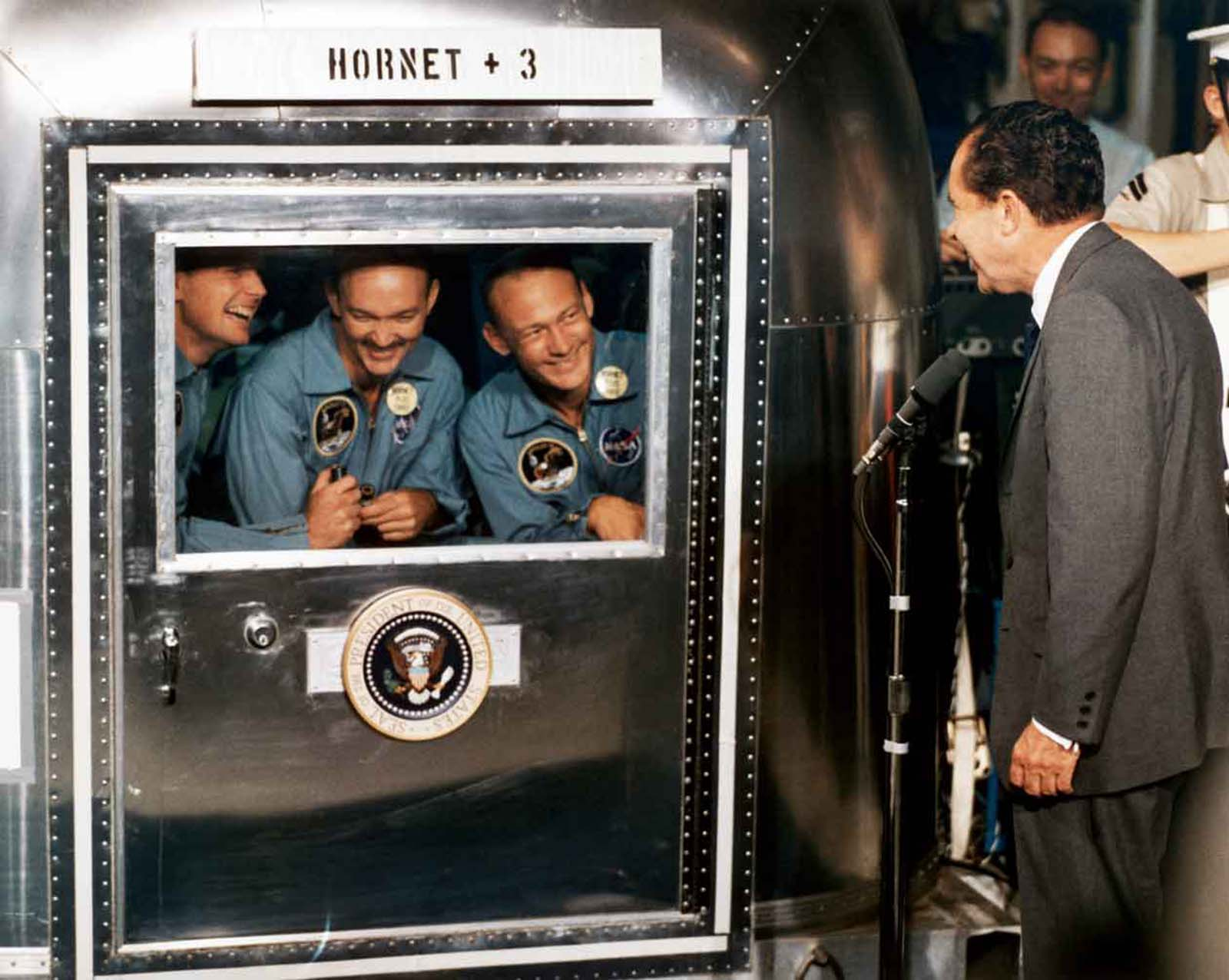 After Apollo 11 returned home, (left to right) Neil Armstrong, Michael Collins and Buzz Aldrin, in mobile quarantine facility, received a visit from President Richard Nixon (July 1969).
