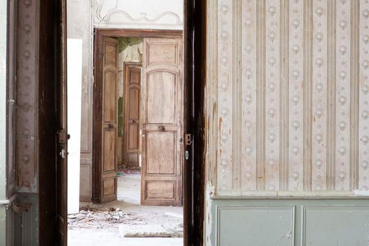 Stripped wallpaper and antique wood doors in Chateau de Gudanes