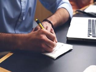 ragazzo che scrive con la penna