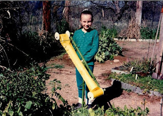 A young girl in a green outfit standing in a garden holding a long yellow cylindrical insect trap.
