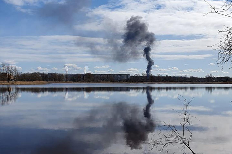 Degošo atkritumu dūmi atspīd ūdenī