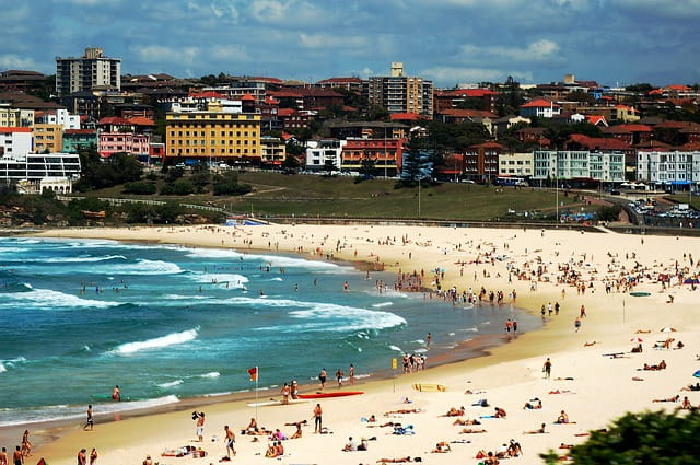 Bondi beach filled with beachgoers getting a tan, swimming, and surfing