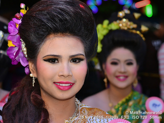 Matt Hahnewald; Facing the World; people; portrait; head shot; night shot; colour; flash; Nikon DSLR D3100; 50 mm prime lens; Nikon SB-400; Asia; Southeast Asia; Northern Thailand; Chiang Mai Province; Mae Chaem; Yi Peng; beauty contest; beauty pageant; Thai beauty; beautiful; Lanna culture; costume; make-up; flowers in hair; red lips; eye contact; world cultures; travel; travel destination; false eyelashes; tarted up; dolled up to the nines; necklace; drop earrings; village beauty; hairdo; yellow orchids; double portrait; duo portrait