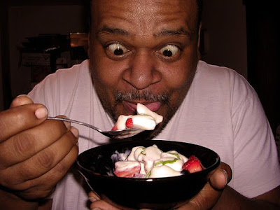 Man Hungrily Eating Fruits Mixed with Yogurt