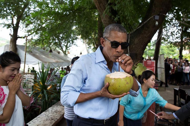 The reaction on coconut seller's face as Obama patronizes her wares