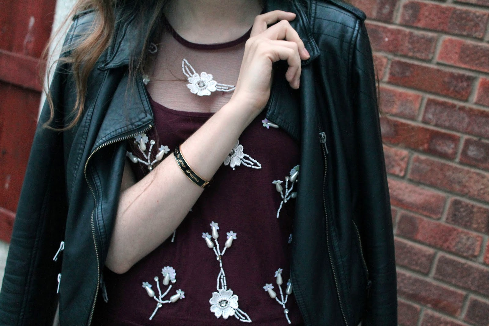 disney couture asos bracelet with glamorous embellished top and leather jacket worn over shoudlers