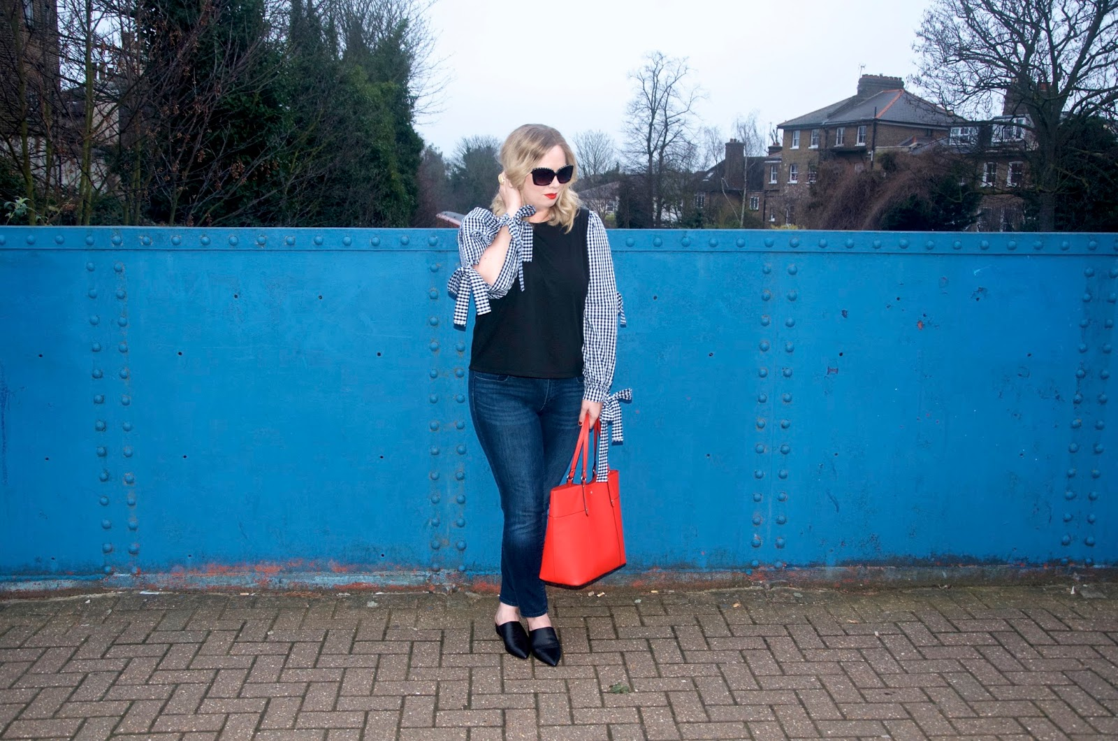 sunglasses, gingham sleeves with bows, red bag, black mules and blue bridge