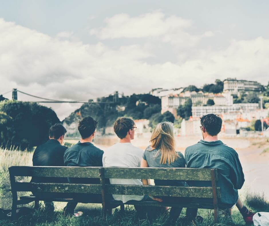 Four teen boys, and one teen girl sit on a bench in a field with their backs to the camera staring at a city across a river in the distance.