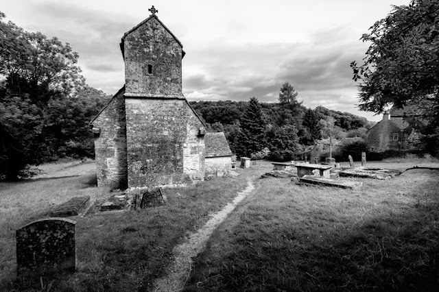 Black and white image of the ancient Saxon church in the Cotswold village of Duntisbourne Rouse