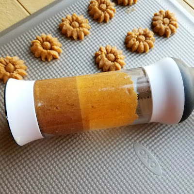 cookie press filled with cracker dough and some crackers pressed out onto cookie sheet