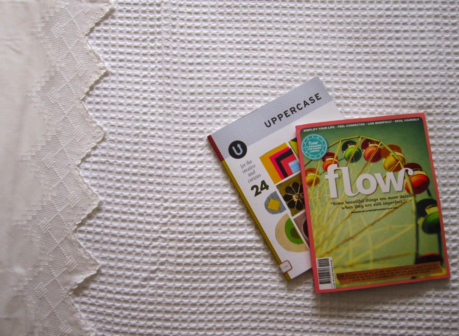 Close up of a freshly-made bed with a white waffle-weave blanket and a copy of Flow magazine and Uppercase magazine on it.