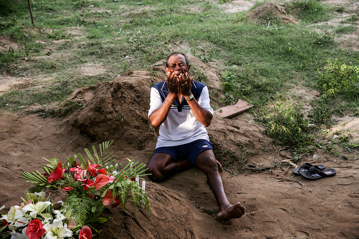 A man mourns at a grave of a victim, two days after a string of suicide bomb attacks on churches and luxury hotels.