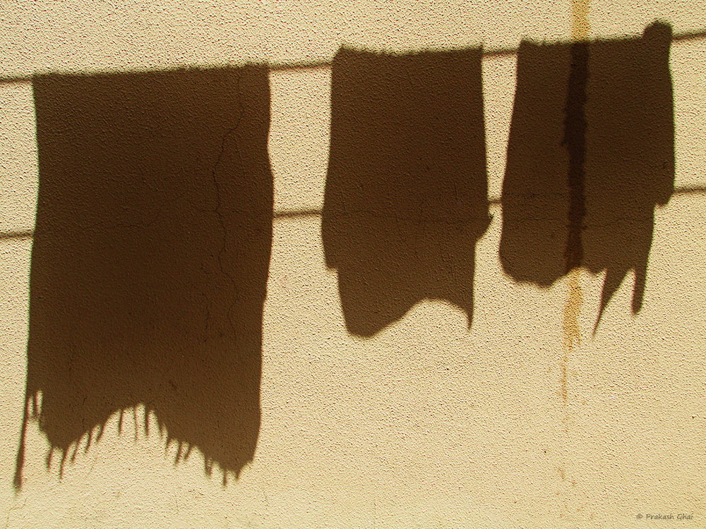 A minimalist photo of Shadow of three clothes drying on a Clothesline