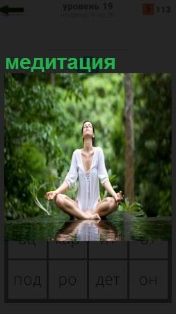 На природе девушка в позе сидя с раскинутыми руками занимается медитацией