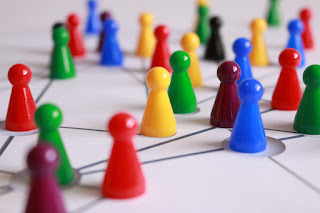 Plastic pawn playing pieces in several colours arranges on a white board with lines variously connecting them.
