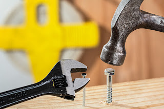 Image shows a piece of wood with a nail and a bolt part-way into the wood. A hammer is held over the nut, and a spanner is held over the nail.