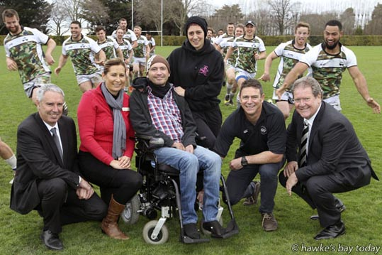 L-R: Lawrence Yule, mayor, Hastings District Council; Jodi Edwards, organiser, The Motor Neuron Disease Walk; Nathan McNabb, Napier, has MND; Donna Spark, his partner; Damon Harvey, co-chair, Jarrod Cunningham Trust; Bill Dalton, mayor, Napier City Council. Running past, members of the Hawke's Bay Magpies Rugby team. Pictured at NOBM, Napier Old Boy's Marist, Park Island, their training ground. Promo for the Motor Neuron Disease Walk 2016, at Hawke's Bay Regional Sports Park, Hastings. photograph