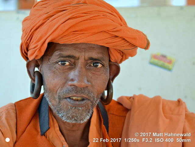 matt hahnewald photography; facing the world; gorakh nath; monk; monastery; bhavnath; bhavnath fair; character; face; earrings; ears; holed; eyes; facial expression; eye contact; stubbly; turban; orange; consent; empathy; rapport; respect; traveling; religious; traditional; cultural; hinduism; festival; event; mela; devotee; pilgrim; junagadh; gujarat; asian; indian; western india; one person; male; elderly; man; picture; photo; face perception; physiognomy; educational; nikon d3100; nikkor af-s 50mm f/1.8g; prime lens; 50mm lens; 4x3 aspect ratio; horizontal orientation; street; portrait; closeup; headshot; seven-eighths view; outdoors; color; posing; authentic; powerful; determined; focused; manly; kanphata; yogi; darshani; gorakhnathi; shaivism; splitted ears