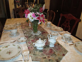 A different set of china with a beautiful floral arrangement, ready for breakfast