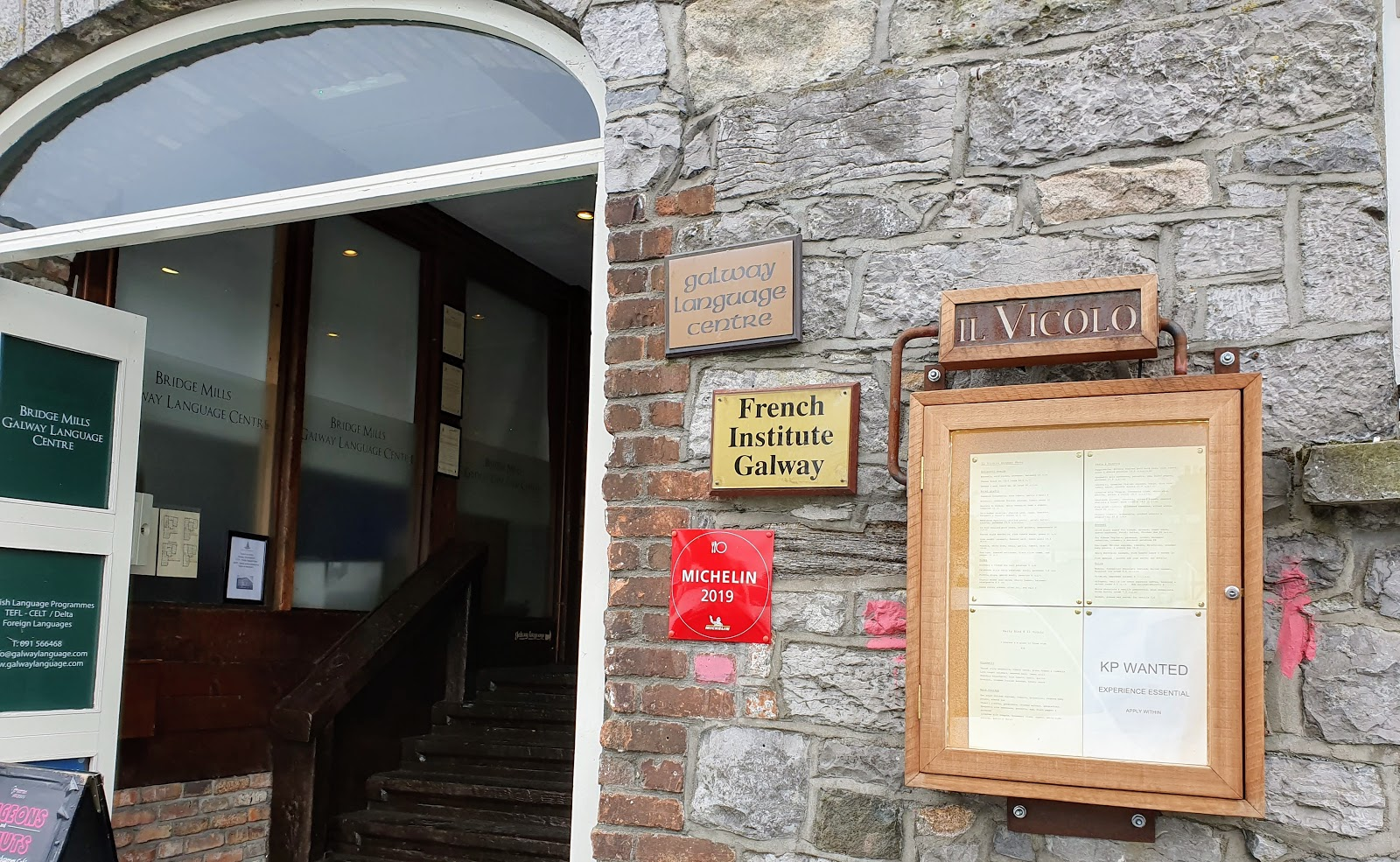 door opening into an upward staircase, nameplates for French Institute Galway, Galway Language Centre and Michelin 2019 for Il Vicolo restaurant - and their menu in a locked wooden noticeboard