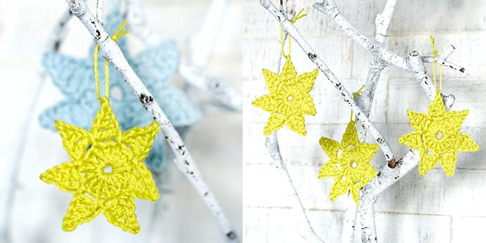 Limefarbene Häkelstern (und ein Mintfarbener Stern) hängen an weißen Ästen.