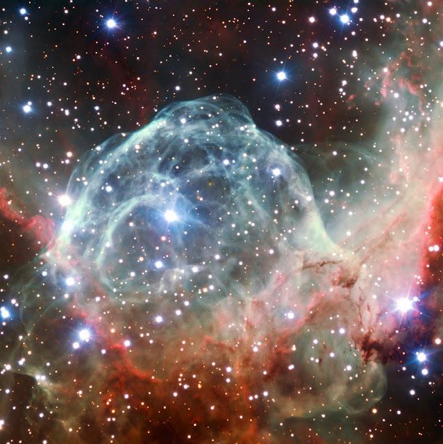 Resultado de imagen de Wolf-Rayet BATT99-49, nos muestra como sus energías producen coloridos tonos en la espesas nubes de gas hidrógeno que ocultan las estrellas nuevas