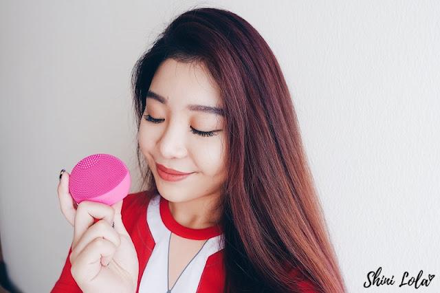 Shini Lola holding a FOREO silicone face brush